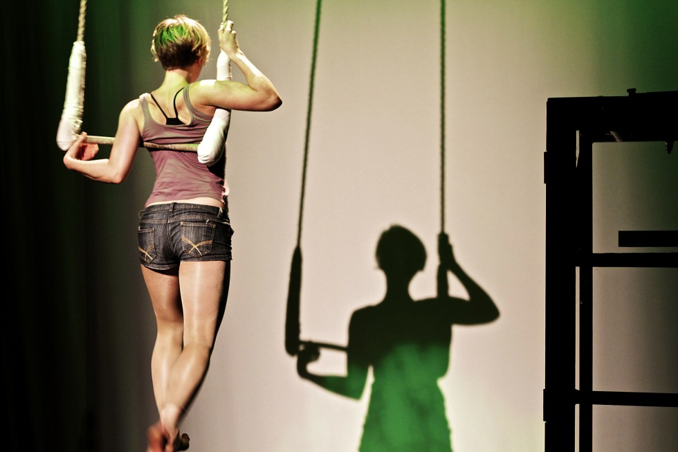 woman suspended on trapeze facing away