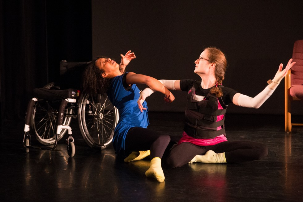 Two dancers seated on the floor with right arms entwined