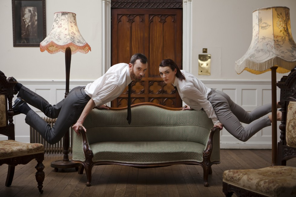 Dancers hover in mid air holding on to a sofa