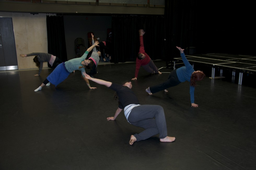 Dancers crouching and reaching one arm up