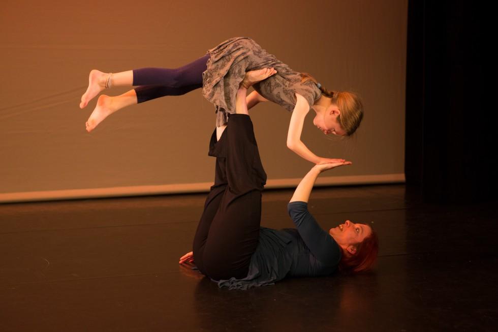 Girl balances on the legs of lying down woman